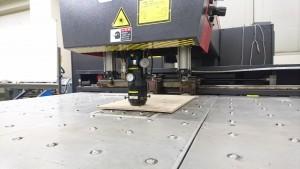 レーザー加工機で穴を切っている最中。予算の都合で安い檜合板で,下降中には檜や加工時の焦げる匂いのワクワクする感じ!